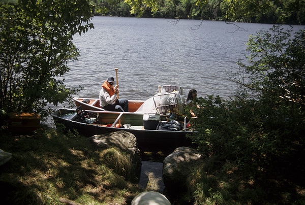 Father and daughter sitting in a loaded canoe.  on shore of Grout pond Southern Vermont