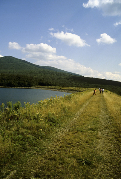 Three women and a boy walking on the earth dam at Some rset Reservoir, Vermont