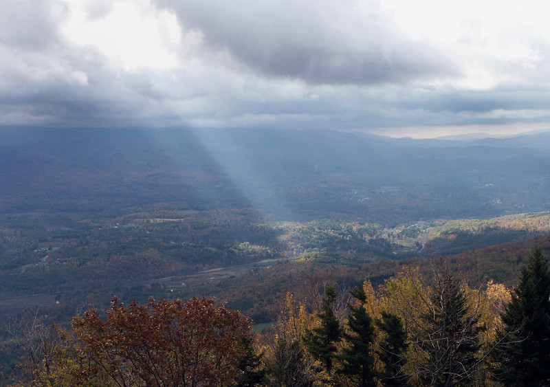 A horizontal stock photo showing a Scenic view from Mt. Equinox Vermont showing a strong sunbeam.