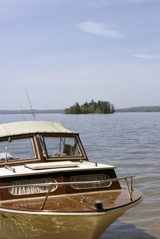 A stock photograph showing a wooden cutty cabin grady white boat on the shore of a wilderness lake in southern vermont