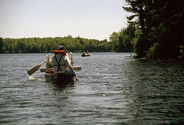Four people in two canoes paddling to their campsite on Grout pond,southern vermont.