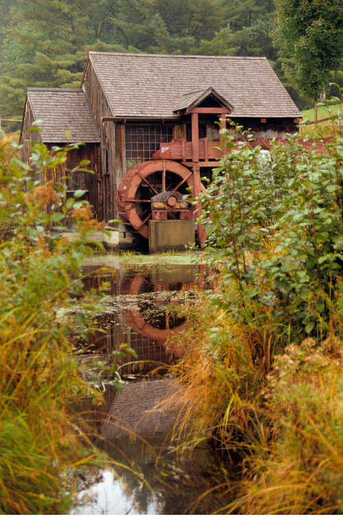 A vertical stock photograph of a water powered Grist Milll located near Guildhall Vermont.