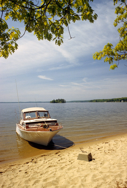 Vertical Stock Photograph of a Wooden cuddy cabin boat tied up to shore of Somerset  lake in Southern Vermont