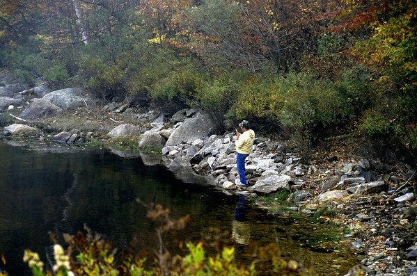 A stock photograph of a young man fishing the shoreline of Somerset reservoir on a beautiful autumn day.