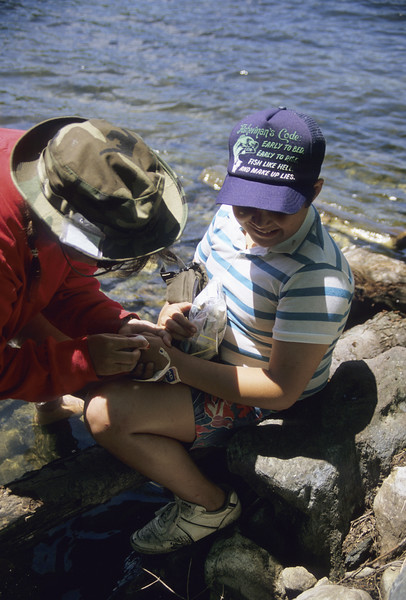 Teenage sister applying first aid in a wilderness setting to a small cut on her  brother's hand