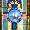 Stained glass window depicting a ship representing the Church as God's vessel of salvation.