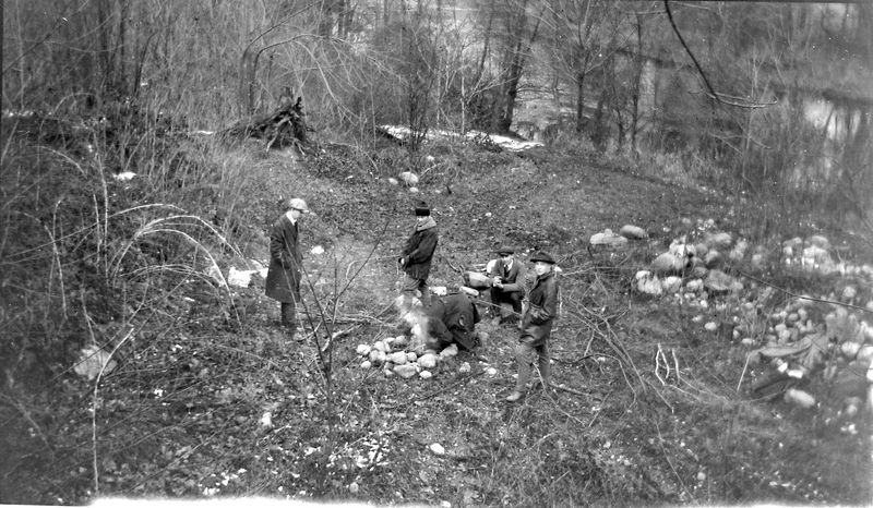 #1 young men by river starting fire maybe Boy Scouts