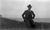 #2 Rowland Stebbins sits on rock wall ocean behind