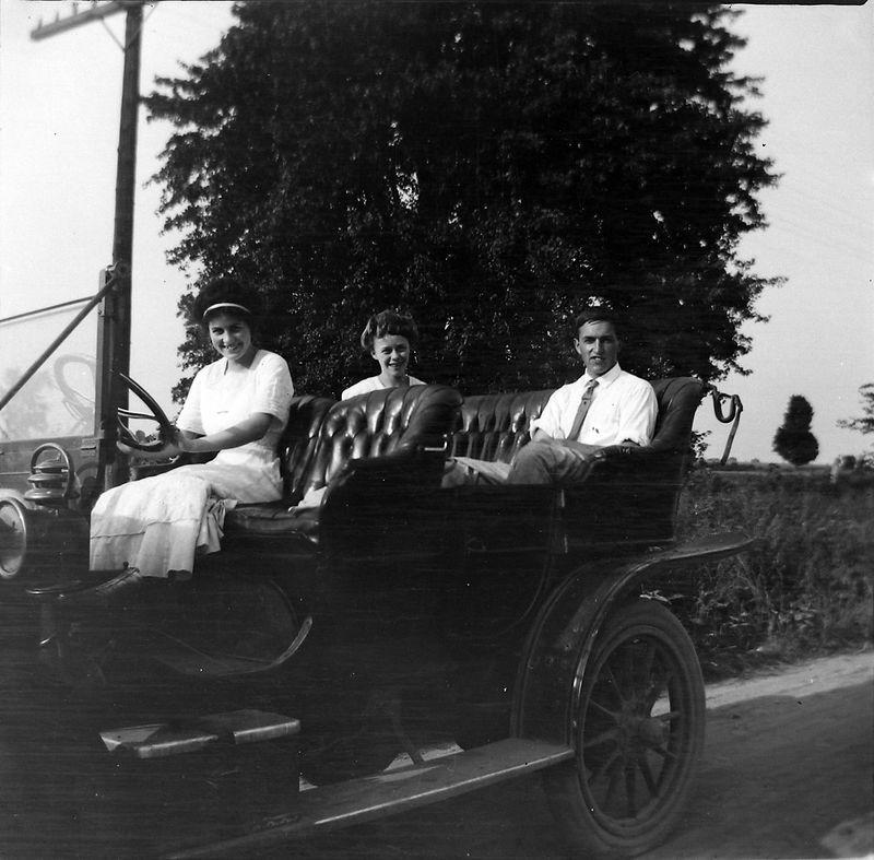 #1 two women & a man in open car
