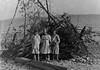 43-ma Three girls by Roaring Brook bonfire woodpile