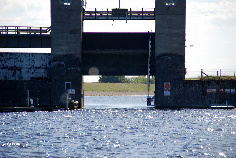Approaching Parteen Weir from Killaloe. Note the barriers (raised in the photo), one either side of the guillotine gate.  Normally the gate will be in the closed position and boaters will be required to alight at the floating jetty on their port side and enter the necessary PIN number (changes weekly .... contact Lock-keeper at Ardnacrusha for current number) in the provided keypad. Note that it takes approximately 20-25 mins for gate to be raised.