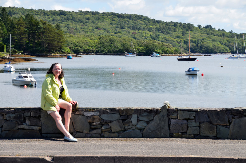 Ashore for one of our shopping expeditions, Mary takes a moment to relax against a backdrop of Glengarriff Bay..