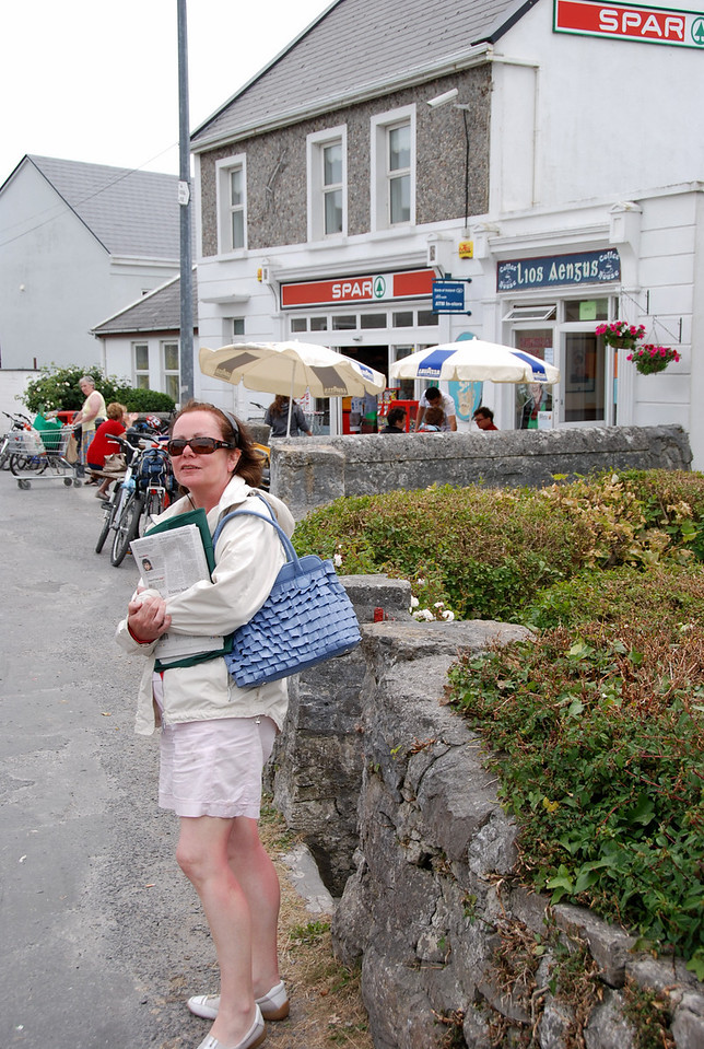 Mary, outside the only Foodstore/Newsagent on the island. Opens at 09.00 and closes at 19.00. Newspapers usually not available until after 11am.