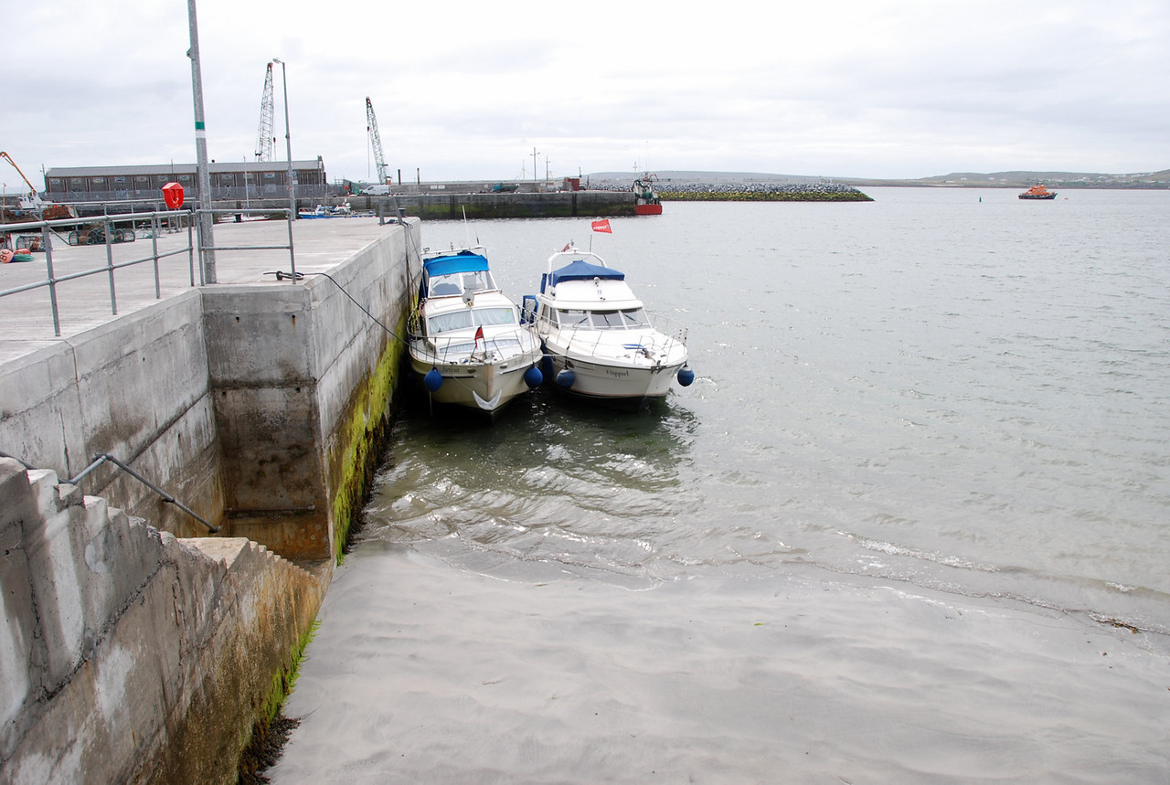 "The tide is going out!  ""Arthur"" and Rapport moored at the short pier, just in front of Carraig Donn gift shop and close to several bars and restaurants."