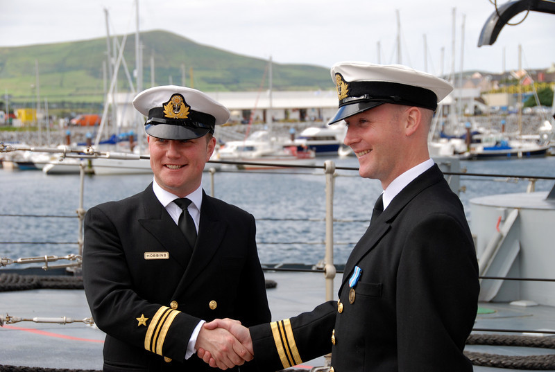 Outgoing and incomng captains share a handshake after the official ceremony.