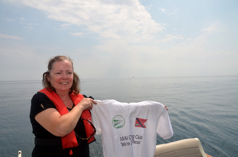 Mary holds up a Cruising Club T-shirt with the club's slogan...'We're Going Places'.  And in the distance can be seen the Fastnet Rock as we head for Crookhaven.
