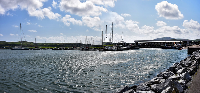 Dingle Marina with service block on right which includes restaurant, shop, office, toilets, showers. Note large yacht on left of picture.