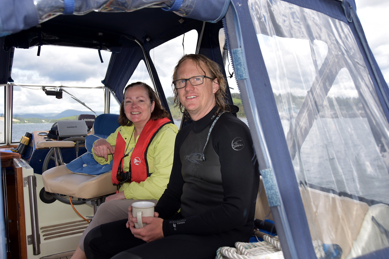 """circa 12:55... Yes, that's a three hour interval since the last photo/video!<br /> <br /> Well, we had an exciting time once we arrived in Bantry Harbour. The wind blew up (F5) and we experienced great difficulty in securing a visitor's mooring buoy. It's always easier for yachties!... They can lie down on the deck near the bow and reach down to secure a line to a mooring buoy. Mobos have it more difficult because of the height between deck and water! <br /> <br /> First problem was actually picking up the lead line and even when we managed that the fun was only starting. We simply could not secure a line to the mooring buoy and in the process we lost our trusty Moorfast... the plastic head simply broke off as we tried to use it to secure a line to a mooring buoy... :-(<br /> <br /> We considered some options... head back to Glengarriff and hope that it might be easier to secure a mooring buoy there, or head back down to the sanctuary of Lawrence Cove Marina and a solid berth.<br /> <br /> BUT, in the end we tried a third option...We contacted the Bantry Bay Harbour Master and explained our predicament. He insisted that we hold fast and he then got into his car and drove out to the harbour and got into his own boat and sailed over to where we were and enabled us to secure a line to a mooring buoy.  However, in the process I got a nasty feeling that the line had got tangled under Arthur's hull. The Harbour Master contacted a local diver, Diarmaid Murphy (pictured above with Mary), who came out and cut the tangled line before re-connecting it to the mooring buoy.  And we also discovered that Diarmaid, together with his wife, runs a local fish restaurant, the Fish Kitchen (more later). <br /> <br /> So, all's well that ends well. And having secured Arthur, and with the wind having reduced somewhat, we hopped into our dinghy (""""Baby Arthur"""") and headed over to the new pontoon and then walked into town, approx. 10-15 mins depending on your walking speed!"""