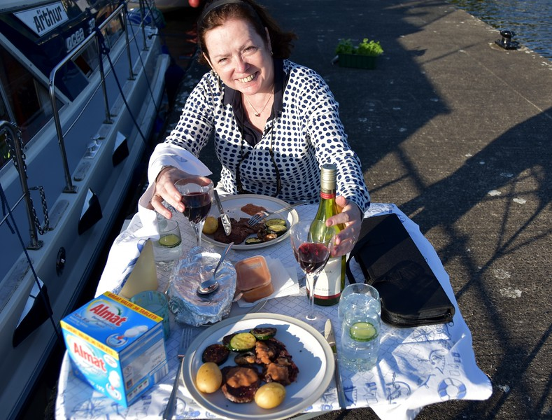 So what is a box of Almat washing tablets doing on the picnic table? And a small toolkit in a black carry case? And Mary with one hand on her glass of red wine and the other on the remnants of the bottle of white wine.<br /> <br /> One word by way of explanation...wind!  It had become gusty during the evening as we attempted to enjoy our BBQ on the quayside. So much so that the tablecloth was being caught by the wind and would have taken the entire contents of what was on the table with it unless we secured it!