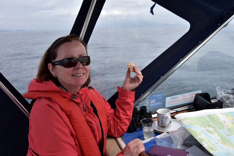 Circa 14:15 ...Mary enjoying a sambo and a cuppa! And the smile might have something to do with the fact that we have already encountered dolphins on this passage!