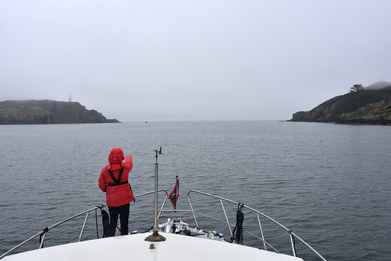 09:40...we make our approach to the mouth of Baltimore Harbour. But visibility is not good!  Mary points towards the buoy that marks Loo Rock at the mouth of the harbour.
