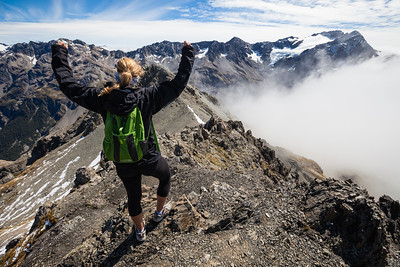 Female walker (20's) raises arms in front of mount Rolleston. Avalanche Peak, Arthur's Pass