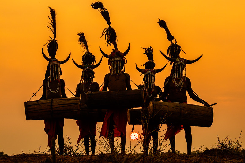 Bison horn (Maria) tribal dancers in the mostly rural state of Chhattisgarh, India, against the setting sun. The silhouettes and backlit color of the dancers' robes are striking; choosing an exposure to show some details of the white necklaces and head dresses adds further interest. [Page 36]