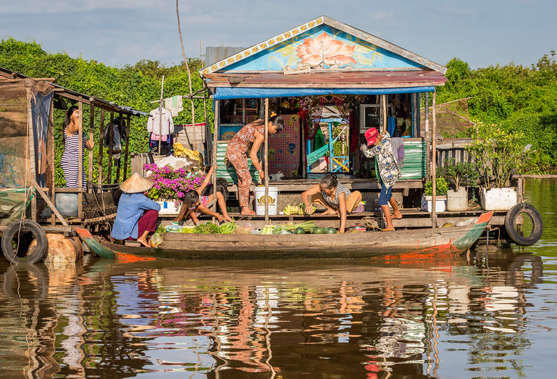As a Mekong River cruise ended in Cambodia's Tonle Sap Lake, we sailed past floating villages, including this beautiful scene of a fruit and vegetable vendor making an early morning visit in her boat to a floating home. [Pages 38-39]