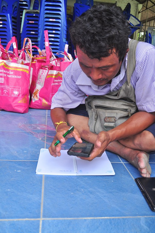 Jonat, one of the Myanmar leaders, diligently calls the recipients one by one to come to collect the Happy Bags.