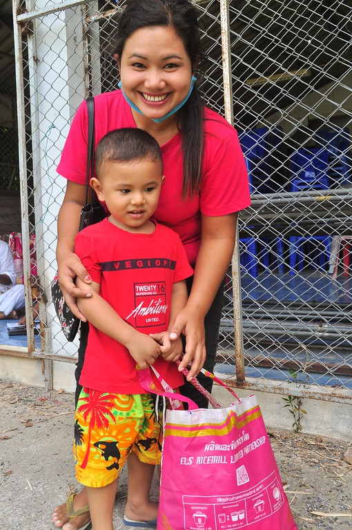 After receiving the Happy Bag, a recipient and her son smile brightly.