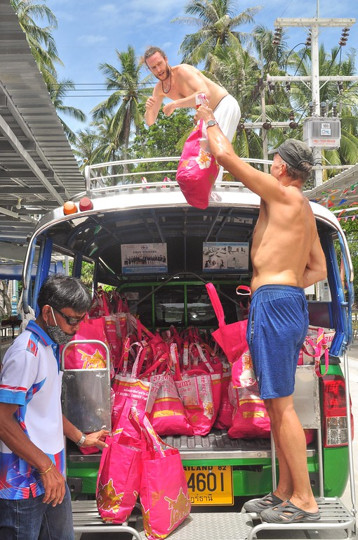 Both local and foreign volunteers help to upload the 300 Happy Bags to the trucks.