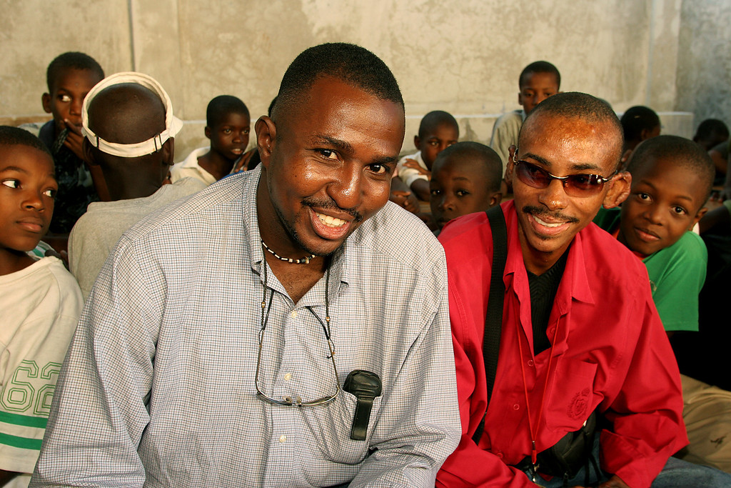 """February 4, 2010 <br>The following is a reflection written by Daniel Tillias, Haitian activist and Project Director of Pax Christi, Haiti.  (<em>Photo: Daniel and Vladamire with children at St. Claire's Parish</em>)  <span style=""""color:#CC9900""""><strong>The Earthquake in Haiti Can Be a Sign for Peace in the World.</strong> </span>  <span style=""""color:#CCCCCC"""">The effort to bring relief to the Haitian people is without precedent. Haiti once again is the center of the world's attention - people from all over, from all religions, all colors and all races are down in Haiti. Many organizations are trying their best to bring assistance to the needed population suffering from the disaster, but it does not seem that it can be enough to help this nation which is recovering from so many lost.   The official number of people who died is close to 200,000; more than 200,000 are injured and the financial loss is evaluate at several billion.   Contrary to previous tragedies like the hurricanes Jeanne and Ike, this past quake has hit all sectors of the country. Everyone had a reason to shed tears in memory of a close family member, relative or friend. Churches and schools that have a hundred years of stories collapsed, with traditions and beliefs that were the foundation of life in Haiti.   If, as it is for the hurricane, they could name an earthquake after something or someone, the name """"professor"""" would fit exactly with this earthquake. Because in less than one minute, Haiti and also the entire world have received a lecture from Mother Nature: the most imminent professor there could ever be.   For many people it is because of the extreme poverty in Haiti that the world has expressed such an attention to this disaster. Maybe it is true, however, something more powerful is behind this. For too many years humanity was lost. Individualism and selfishness were so predominant that we forgot that this earth is all we have so far. We have seen billions spent on nuclear weapons and weapons"""
