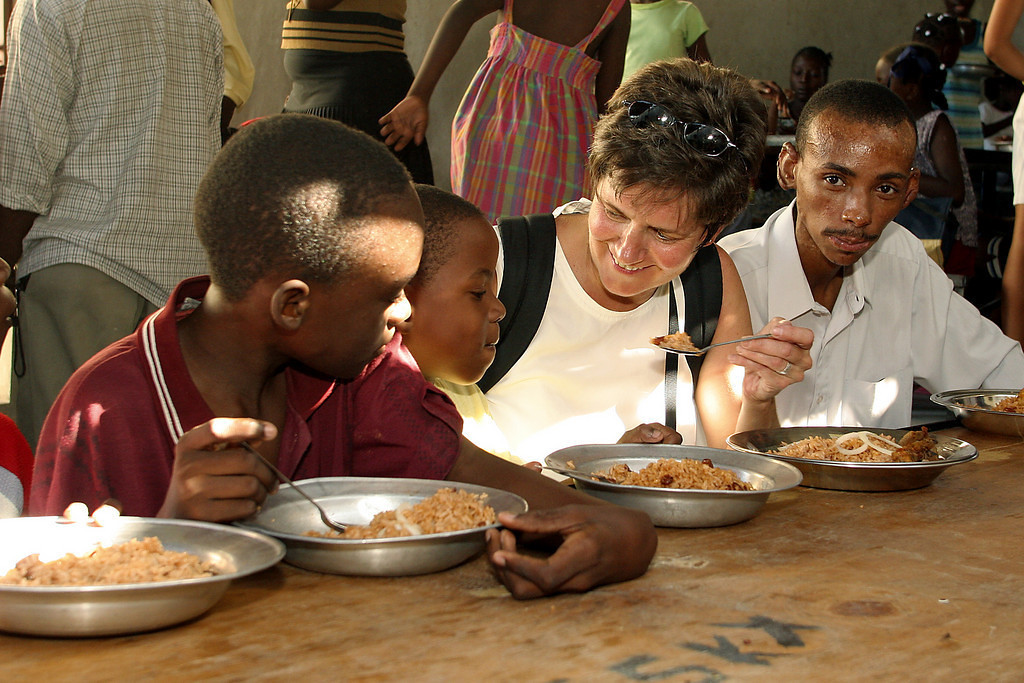 """<a href=""""http://www.opticalrealities.org/GuestProfiles/Johanna-Berrigan/"""" target=""""_blank"""">Johanna Berrigan</a> reporting from Haiti (January 29, 2010). <em>Photo (2004): Johanna and human rights advocate Vladamir spend time with the children at St. Clare's Church, Delmas, Port-au-Prince.</em> <span style=""""color:#CCCCCC""""> 1/29/10 Dear friends,                                                           <br>                                  Another day is winding down. Before I go out to the tent, I decided to send at least a little something like I said I would. Each day has been this incredible combination of bearing witness to overwhelming destruction, suffering and death. At the same time we are with people who exhibit such courage, hope and faith. I am in awe of the outpouring of compassion and help from all over the world. Yet, so many people in these poor communities still have not received food, water or tents for shelter. A priest from one of the local parishes here in Port au Prince said,"""" The emergency medical relief is about over, now everyone needs food, water and shelter."""" He, along with anyone we have spoken to, lives in fear of what will happen to the people when the rains come. It is awful to think about; everyone is living on the streets . A """"fortunate few"""" have tents, but most are living in makeshift """"sheet tents"""" as Bill Quigley called them. We are trying to get information about aid distribution and why it is not reaching these communities.  <br> We are trying to investigate what is being brought in because we have seen no sign of food and water being distributed by anyone. People are begging for tents. We understand that there are tents available, but they are not being distributed because apparently the UN doesn't want the people to stay in the city. They want them to go to organized displaced persons camps outside of Port au Prince. For all of the promises made by our administration to not abandon the Haitian people in their hour of need, the Hai"""