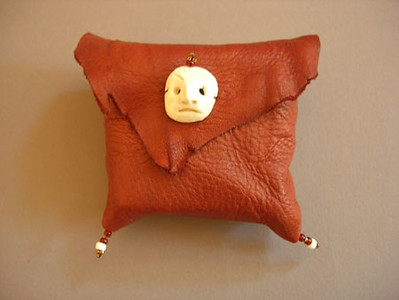 leather pouch with ceramic mask....for book on n ext page