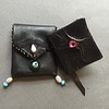 Miniature leather book with eye on cover, plus pouch