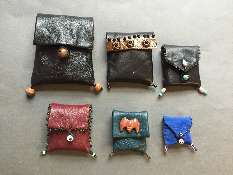 Series of small leather pouches with miniature books inside