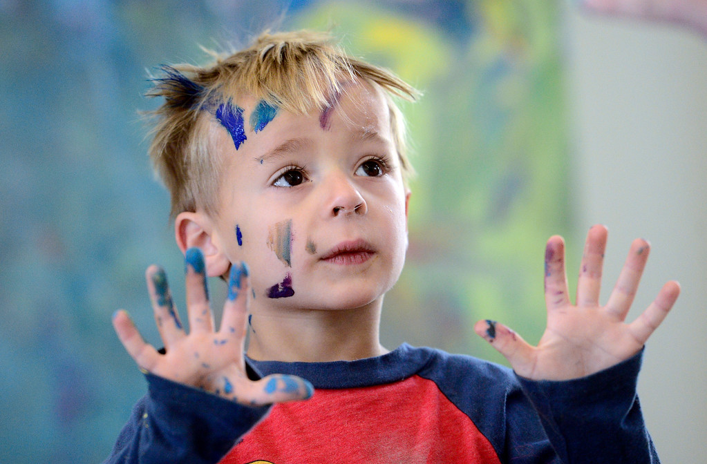 . Pre-K student Lucais Fischaber shows the teacher the paint on his hands while painting with artist Will Day at the Jay and Rose Phillips Early Childhood Center inside the Boulder JCC on Wednesday. Jeremy Papasso/ Staff Photographer 12/06/2017