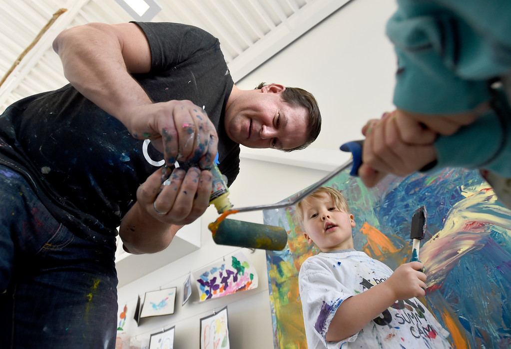. Artist Will Day puts paint on a roller as Kaius Redquist, 4, watches while painting a canvas at the Jay and Rose Phillips Early Childhood Center inside the Boulder JCC on Wednesday. Jeremy Papasso/ Staff Photographer 12/06/2017