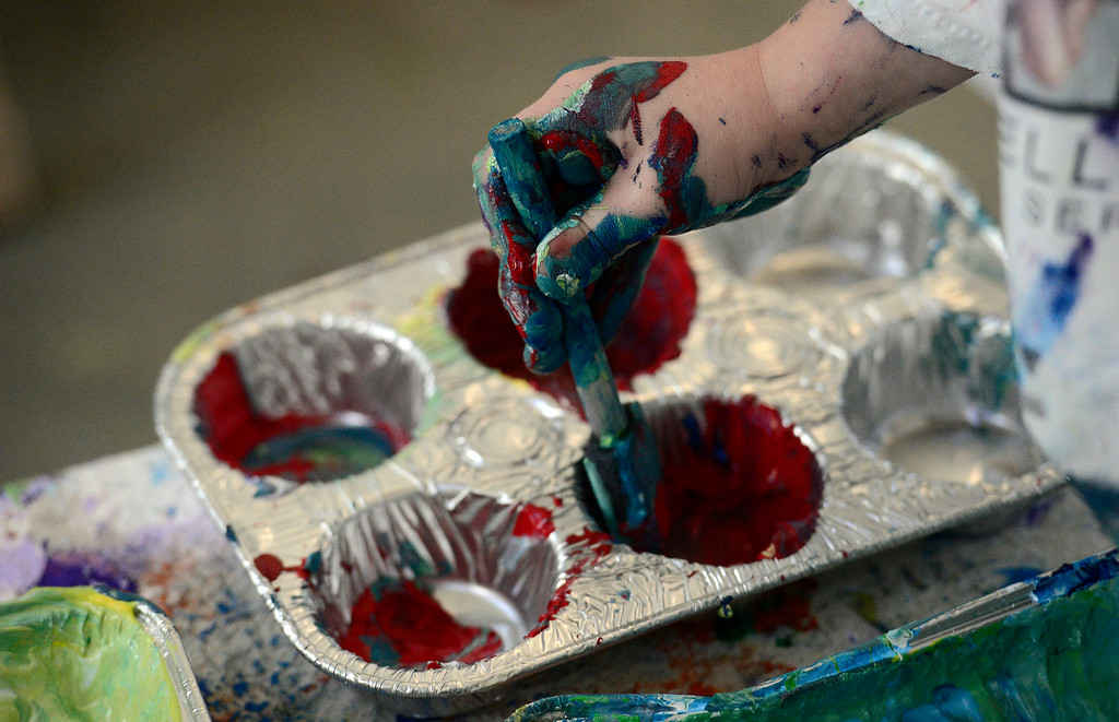 . A Pre-K student puts paint on a brush while painting will artist Will Day at the Jay and Rose Phillips Early Childhood Center inside the Boulder JCC on Wednesday. Jeremy Papasso/ Staff Photographer 12/06/2017