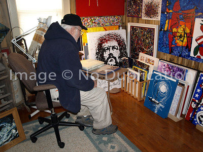 An artist visitor to Star of the North Studio researches photos in the Lake Superior North Shore photo album for his next painting.