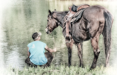 USA, Florida, Horse Haven Ranch.  A man sitting by the water talking to his horse.
