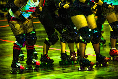 Colorful legs of roller derby female skaters