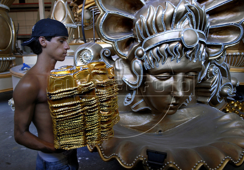 Rafael Sousa, 22, past by a float of Sao Clemente samba school, Rio de Janeiro, Brazil, February 9, 2011. The float will be used during the carnival parades which begin on March 4, 2011. Thousands of people work for more 6 months out of the year preparing for carnival. (Austral Foto/Renzo Gostoli)