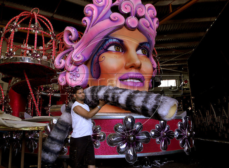 Robert Ramos pasts in front of a float of Sao Clemente samba school, Rio de Janeiro, Brazil, February 10, 2012. The float will be used during the carnival parades which begin on February 18 , 2012. Thousands of people work for more 6 months out of the year preparing for carnival. (Austral Foto/Renzo Gostoli)