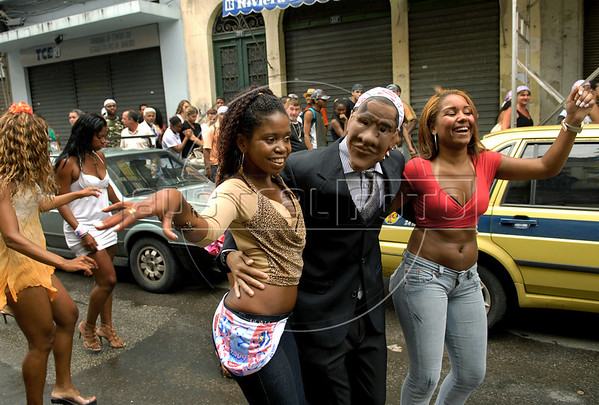 A reveler with a Barack Obama mask and two girls participate in an afternoon street parade during a pre-carnival event in downtown neighborhood, Rio de Janeiro, Brazil, February 14, 2009. (Austral Foto/Renzo Gostoli)