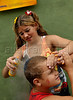 A girl paints the boy's head before participate in an afternoon street parade during a pre-carnival event in downtown neighborhood, Rio de Janeiro, Brazil, February 14, 2009. (Austral Foto/Renzo Gostoli)