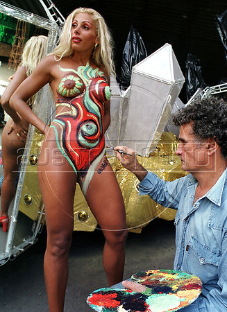 Brazilian plastic artist Albery, right, paints the body of Angela Bismarchi model showing how she will parade in front of Caprichosos de Pilares samba shool drum in next carnival, Rio de Janeiro, Brazil, Feb. 8, 2001. Bismarchi will be the queen of drum, integrated by 300 musicians. Bismarchi who became famous for parading in Rio's carnival with nothing on except a Brazilian flag painted on her, is also known for her many plastic surgeries.(Austral Foto/Renzo Gostoli)