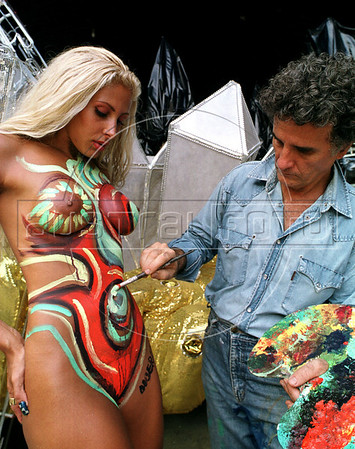 Brazilian plastic artist Albery, right, paints the body of Angela Bismarchi model showing how she will parade in front of Caprichosos de Pilares samba shool drum in next carnival, Rio de Janeiro, Brazil, Feb. 8, 2001. Bismarchi will be the queen of drum, integrated by 300 musicians. Bismarchi who became famous for parading in Rio's carnival with nothing on except a Brazilian flag painted on her, is also known for her many plastic surgeries. (Austral Foto/Renzo Gostoli)