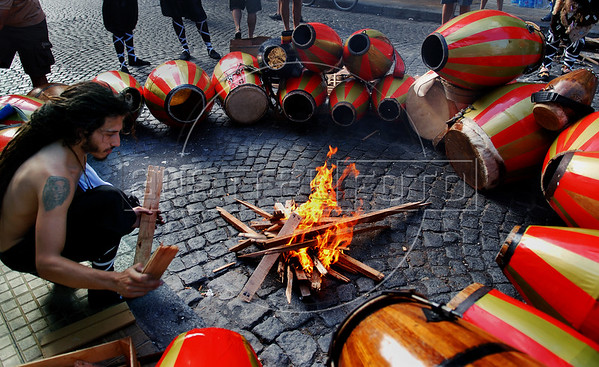 People warms drums at traditional San Telmo district before participate at festivities of candombe, a musical genre originated from the influences of African music and developed on both banks of the Rio de la Plata because of the large influx of slaves during the colonial period, Buenos Aires, Argentina, december 12, 2006. (Austral Foto/Renzo Gostoli)