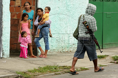 "Dancing with the Devil production stills. Drug traffic ""soldier"" walks past residents in Vila Aliana, Pastor Dione's district. (Australfoto/Douglas Engle)"